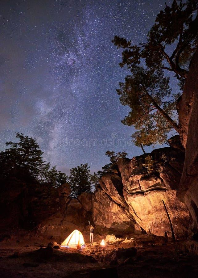 Campingplats på natten Det idrotts- slanka flickaanseendet mellan det lilla turist- tältet och bränningen avfyrar royaltyfria bilder