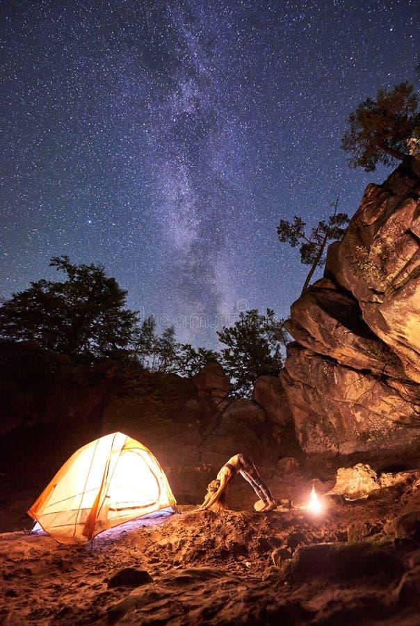 Campingplats på natten Idrotts- slank flicka som gör sträcka gymnastiska övningar på det lilla turist- tältet fotografering för bildbyråer