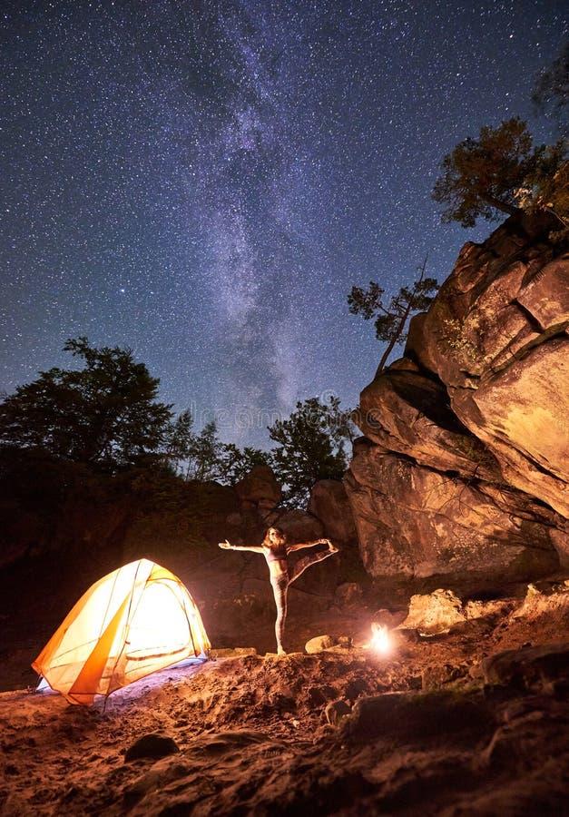 Campingplats på natten Idrotts- slank flicka som gör sträcka gymnastiska övningar på det lilla turist- tältet royaltyfri bild