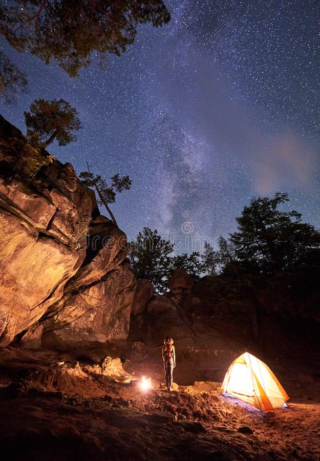 Campingplats på natten Stående raksträcka för barfota flicka mellan det lilla turist- tältet och den brinnande brasan arkivfoton
