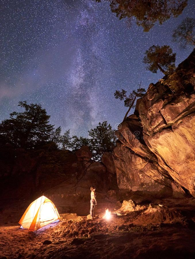 Campingplats på natten Stående raksträcka för barfota flicka mellan det lilla turist- tältet och den brinnande brasan royaltyfri bild