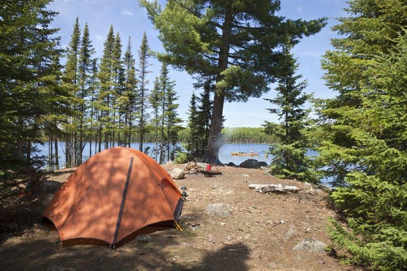 Campingplatz mit orange Zelt und Feuer auf einem Nordminnesota See stockfoto