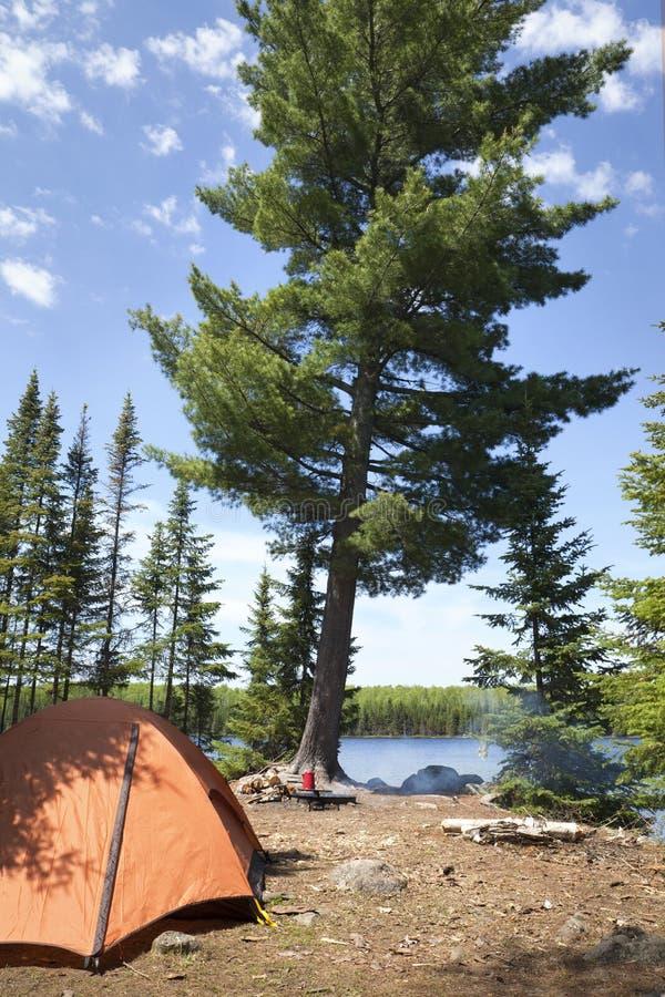 Campingplatz mit orange Zelt und Feuer auf einem Nordminnesota See lizenzfreie stockfotografie