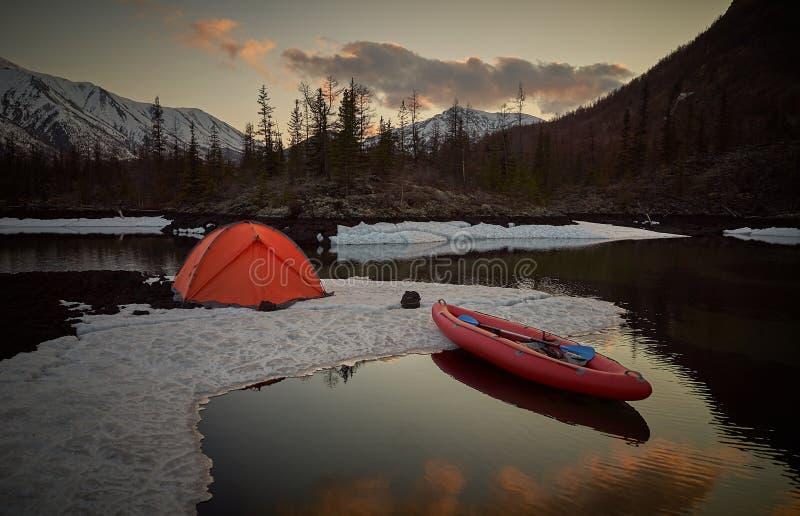 Campingplatz mit orange Zelt und Kanu auf einem See stockbilder