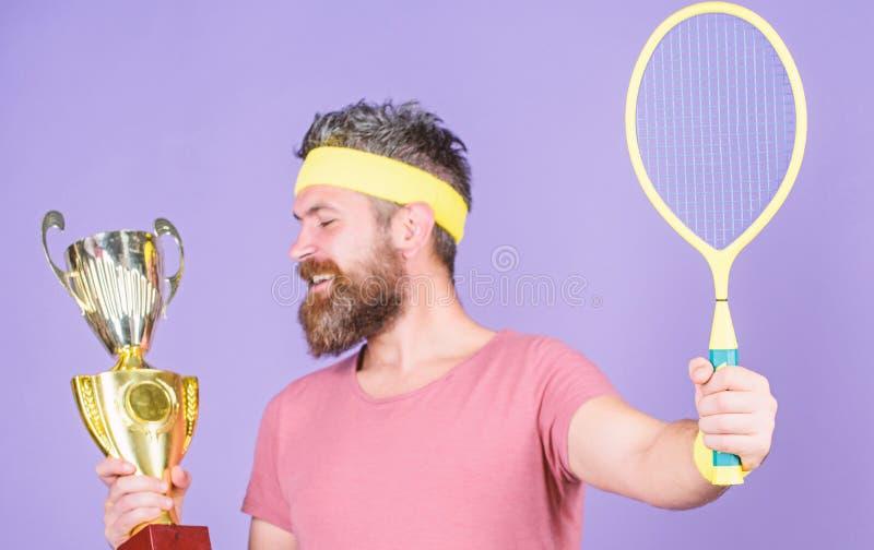 Campionato di vittoria del tennis Racchetta di tennis della tenuta dell'atleta e calice dorato Gioco di tennis di vittoria Usura  fotografie stock libere da diritti