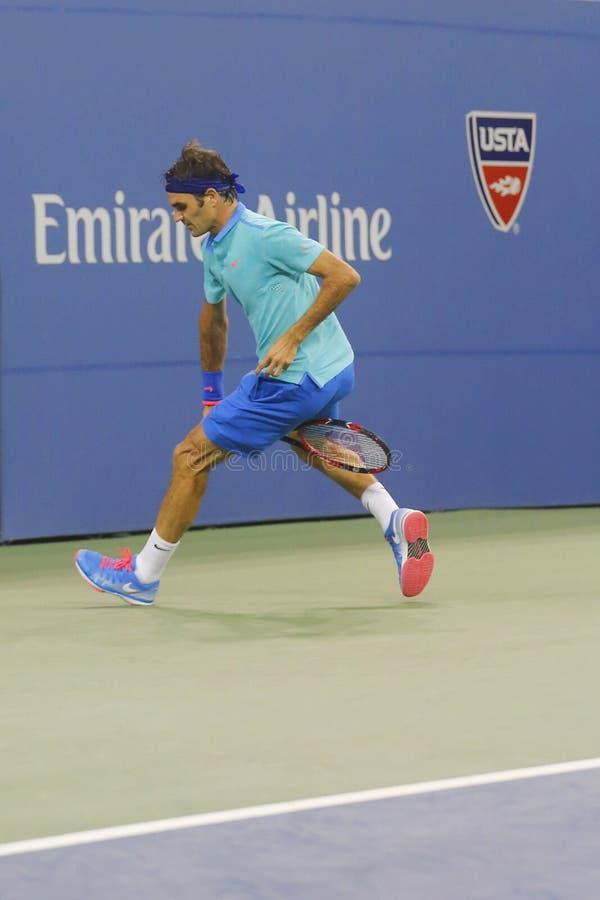 Campione Roger Federer del Grande Slam di diciassette volte che usando Tweener durante terzo la partita del giro all'US Open 2014 fotografia stock libera da diritti