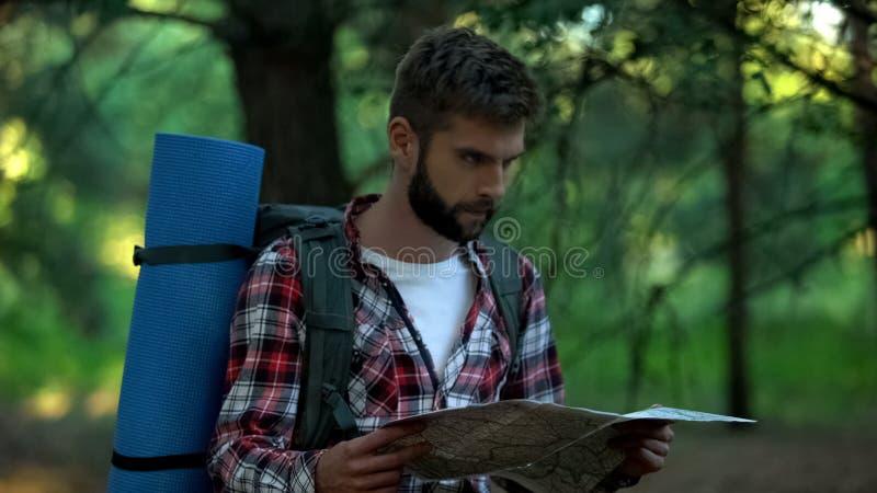 Campista confuso orienteering con el mapa en el bosque, buscando para la manera correcta foto de archivo