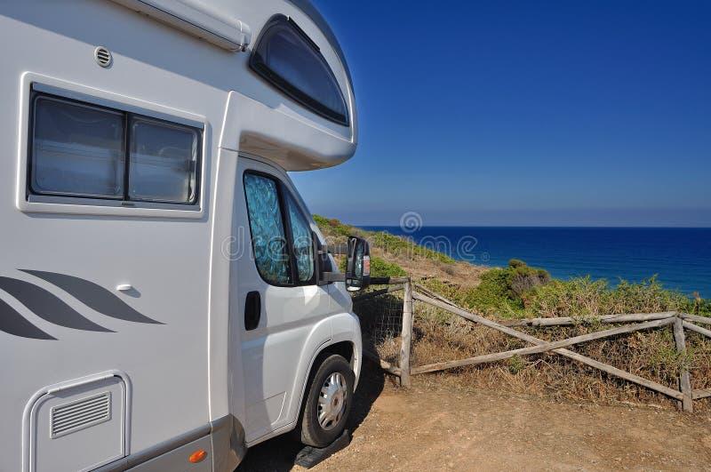 Campista estacionado en la playa foto de archivo