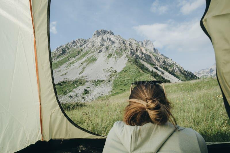 Campista femenino del veraneante en la tienda que mira Mountain View en lunes imágenes de archivo libres de regalías