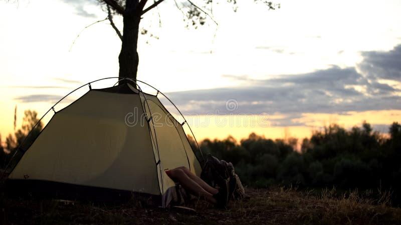 Campista que descansa en tienda temprano en lugar pintoresco, durante la noche en salvaje, salida del sol fotos de archivo