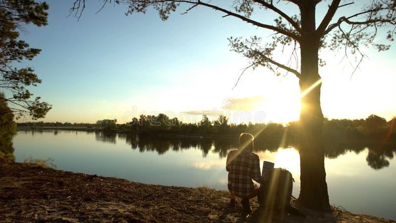 Campista que saca la mochila cerca del río del bosque, gozando sorprendiendo el paisaje, alza fotografía de archivo