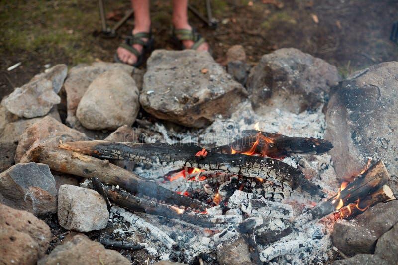 Campista que se coloca junto a una hoguera ardiente imagen de archivo libre de regalías
