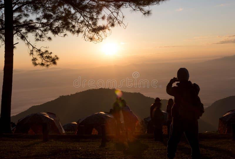 Campistas que tomam uma imagem do nascer do sol com telefone esperto imagem de stock royalty free