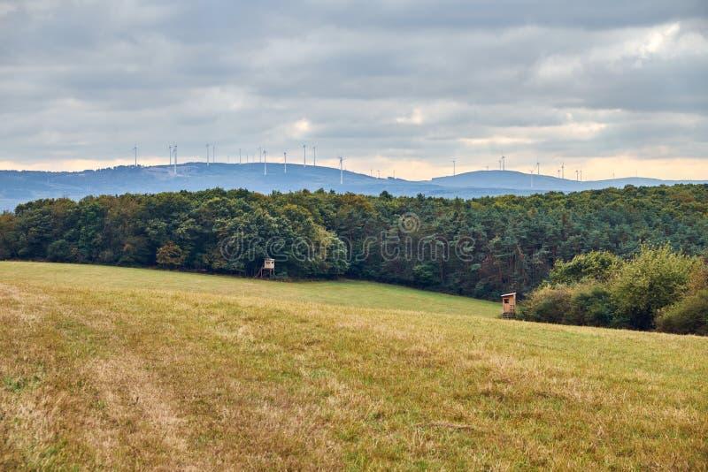 Campo amarelo da agricultura do outono com caça do ponto e de turbinas eólicas de observação de observação em um dia nebuloso na  foto de stock