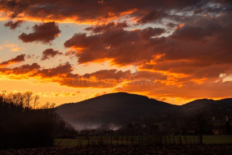 Campo arado e vila da agricultura na noite com as nuvens alaranjadas bonitas fotos de stock