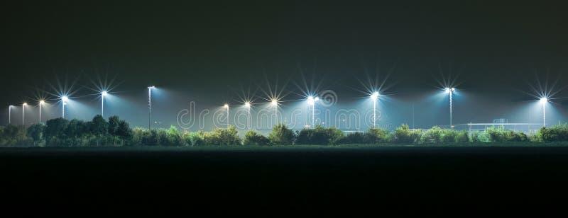 Campo atlético iluminado por luzes brilhantes na obscuridade imagem de stock