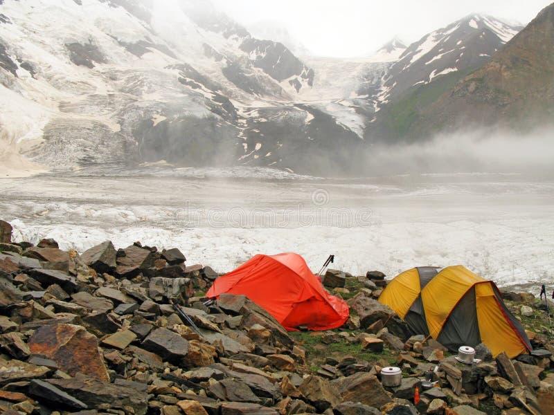 Campo base di scalata di alta montagna contro il ghiacciaio della parete di Bezenghi immagine stock libera da diritti