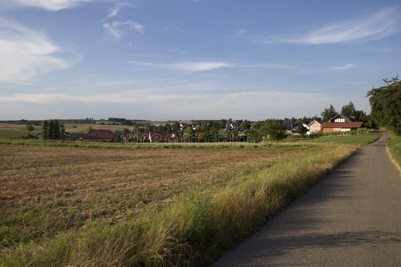 Campo biselado cerca del camino y el pueblo en el fondo imagen de archivo