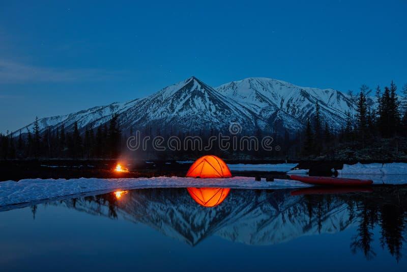 Campo cerca del lago de la montaña Paisaje de la noche con una tienda cerca del agua foto de archivo