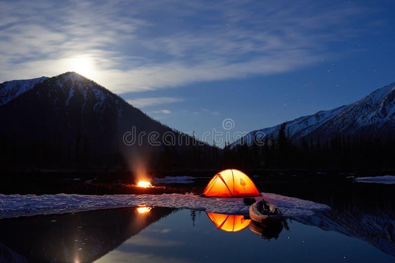 Campo cerca del lago de la montaña Paisaje de la noche con una tienda cerca del agua imagen de archivo