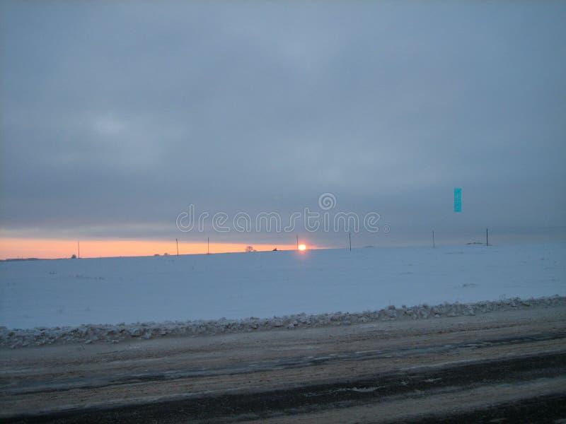 Campo coberto de neve ao longo da estrada na noite do inverno no por do sol imagens de stock