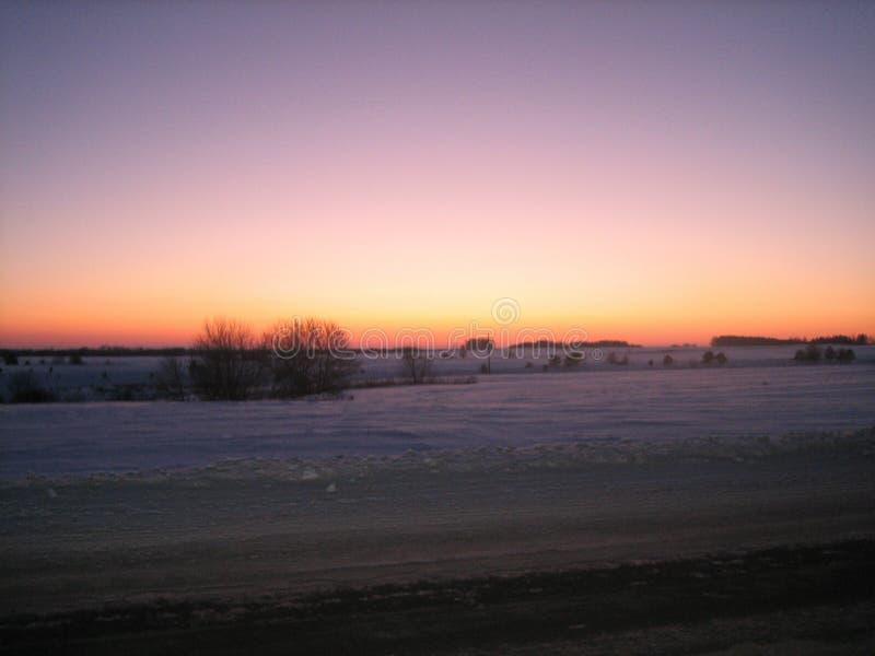 Campo coberto de neve ao longo da estrada na noite do inverno no por do sol imagem de stock