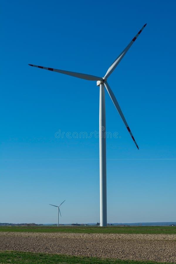 Campo con los molinoes de viento para la energ?a el?ctrica La energ?a limpia produjo por el viento Extracci?n de la energ?a del a foto de archivo