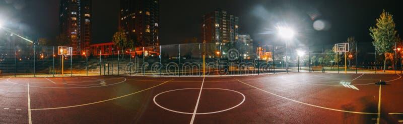 Campo da giuoco illuminato di pallacanestro con pavimentazione rossa, nuova rete moderna di pallacanestro fotografia stock libera da diritti
