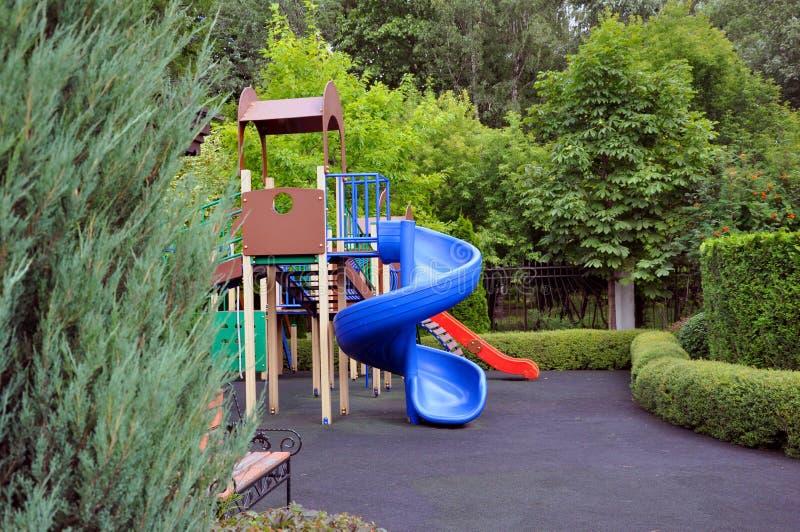Campo da giuoco per i bambini nel parco fra gli alberi verdi fotografia stock