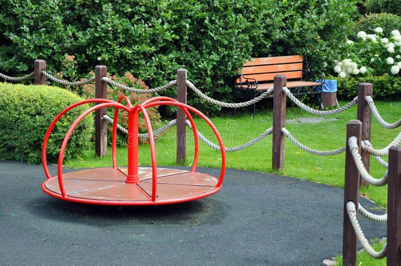 Campo da giuoco per i bambini nel parco fra gli alberi verdi immagine stock libera da diritti