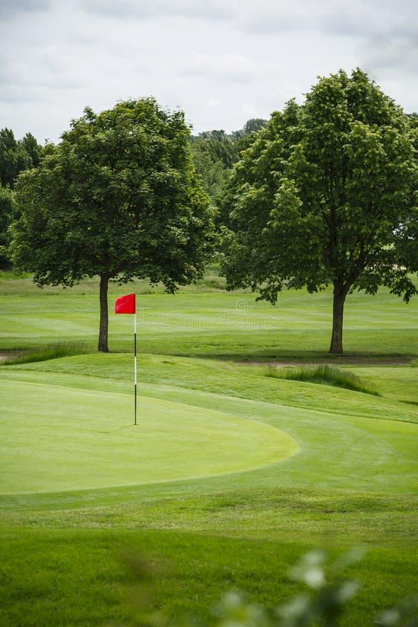 Campo da golf con la bandiera rossa immagine stock