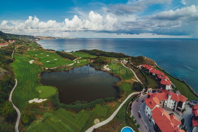 Campo da golf nella località di soggiorno di lusso accanto alle scogliere del mare Siluetta dell'uomo Cowering di affari immagini stock