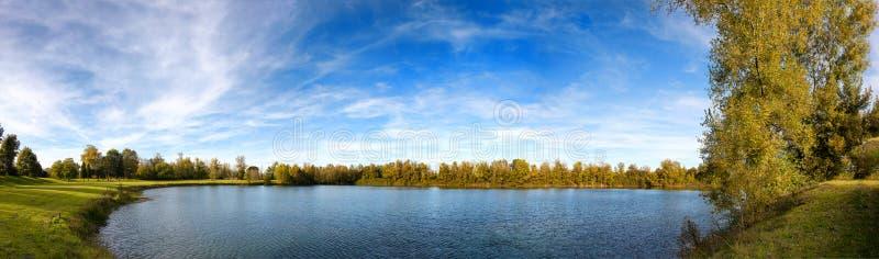 Campo da golf verde con il piccolo lago immagine stock