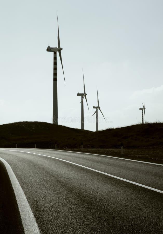Campo das turbinas eólicas perto da estrada fotografia de stock