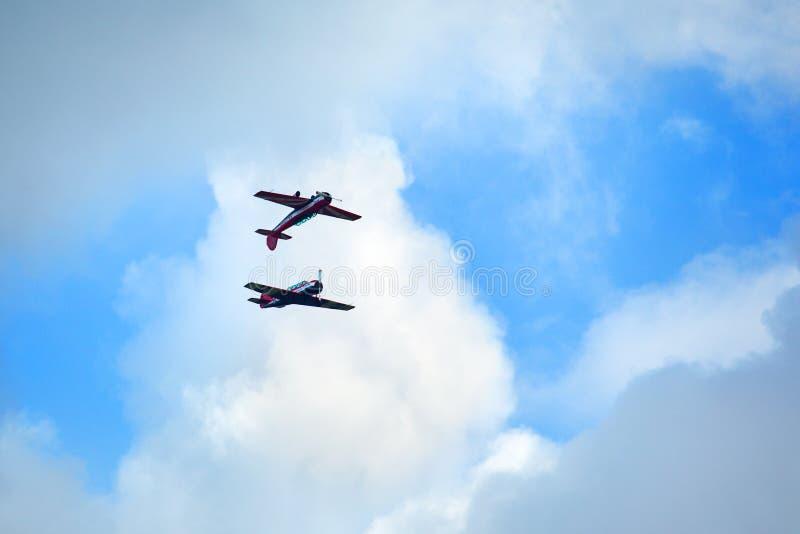 Campo de aviaci?n de Mochishche, sal?n aeron?utico local, vuelo de dos aviones Yak-52 junto, acrobacias a?reas el espejo, equipo  foto de archivo libre de regalías