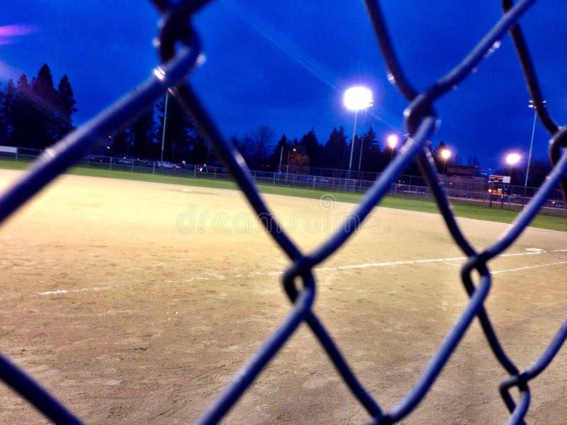 Campo de béisbol y cerca en la noche bajo luces fotos de archivo libres de regalías