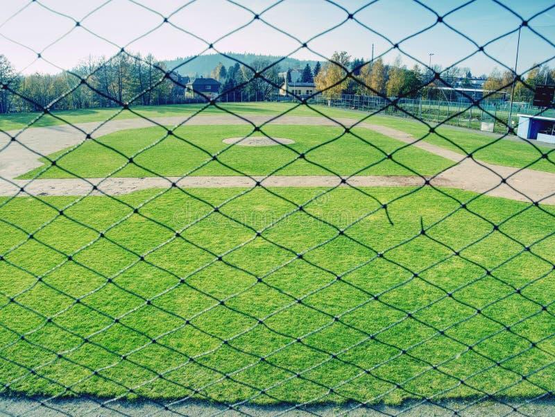 Campo de basebol da juventude visto da rede de trás fotos de stock