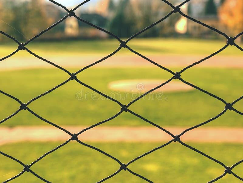 Campo de basebol da juventude visto da rede de tr?s fotos de stock royalty free
