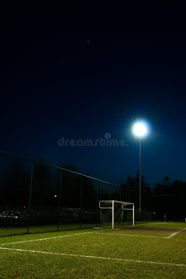 Campo de fútbol encendido en la noche imagen de archivo libre de regalías