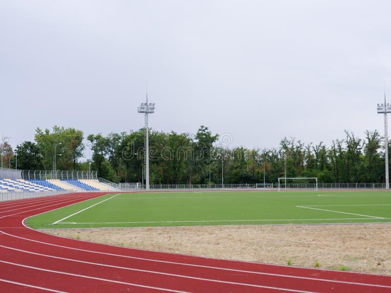 Campo de fútbol verde y pista corriente roja en el estadio Pista corriente en un fondo del estadio Concepto de los deportes copia fotografía de archivo libre de regalías