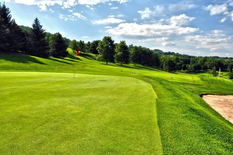 Campo de golf en un día de verano asoleado con el cielo claro imagenes de archivo