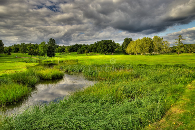 Campo de golfe na iluminação dramática fotografia de stock royalty free