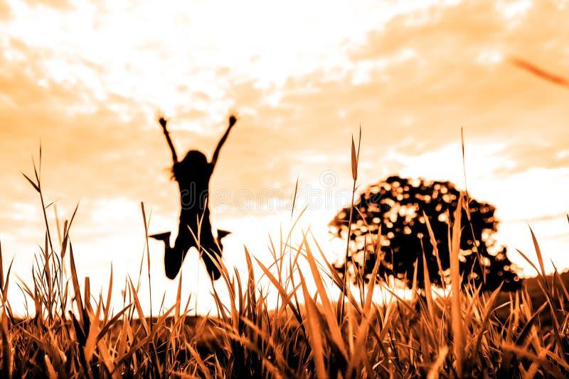 Campo de hierba con el fondo borroso del árbol solo de salto de la persona y del soporte en naturaleza con tono de la puesta del  imagenes de archivo