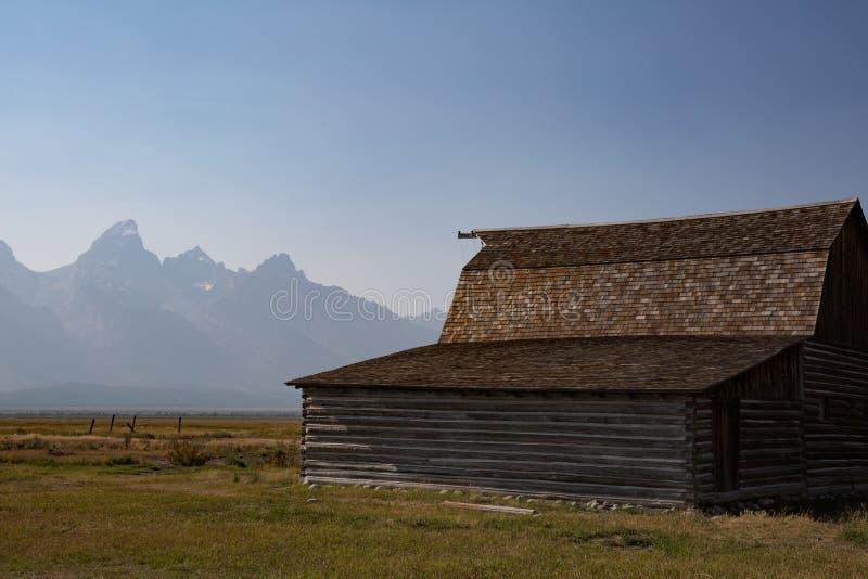Campo de hierba con el granero y montañas magníficas de Teton en fondo imágenes de archivo libres de regalías
