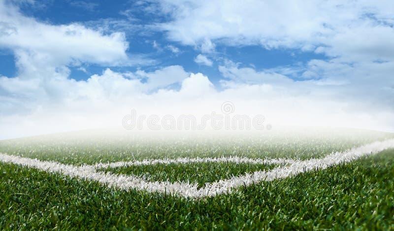 Campo de hierba verde de la esquina del fútbol con el cielo azul imagenes de archivo