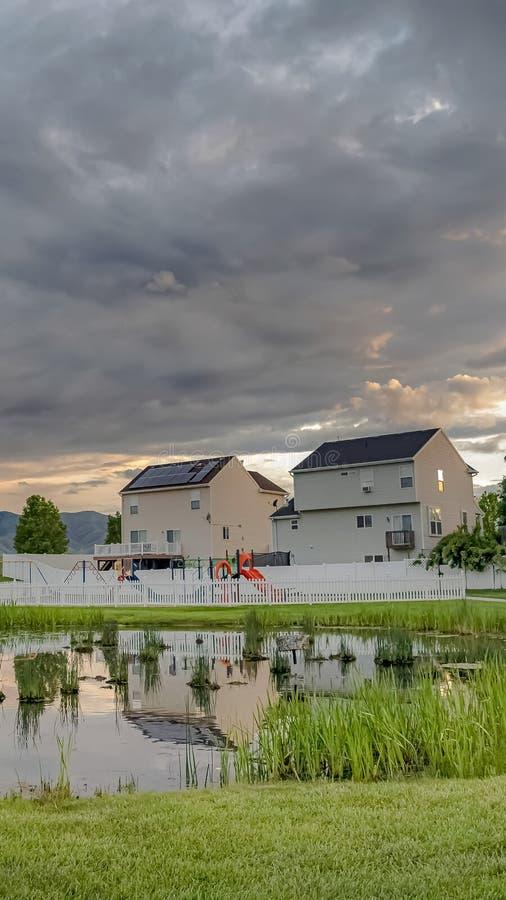 Campo de jogos brilhante vertical da lagoa e multi casas do andar cercados pelo terreno gramíneo vasto foto de stock royalty free