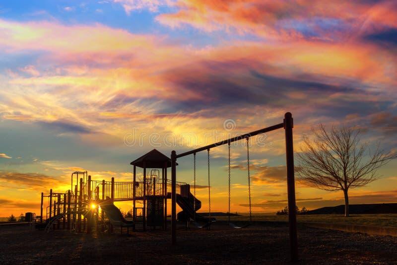 Campo de jogos das crianças no por do sol no vale feliz OU fotografia de stock