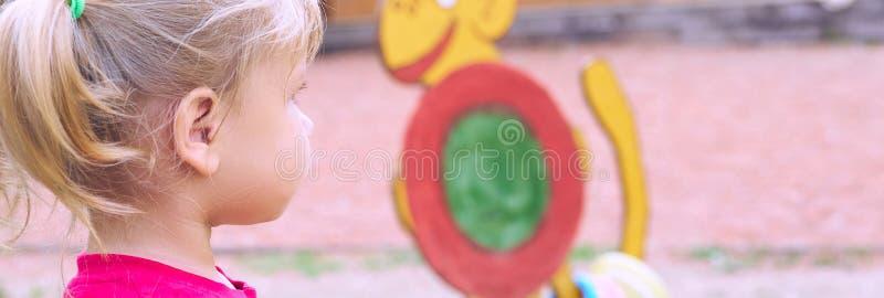 Campo de jogos 2 das crian?as Menina bonito que tem o divertimento no parque público fotografia de stock royalty free