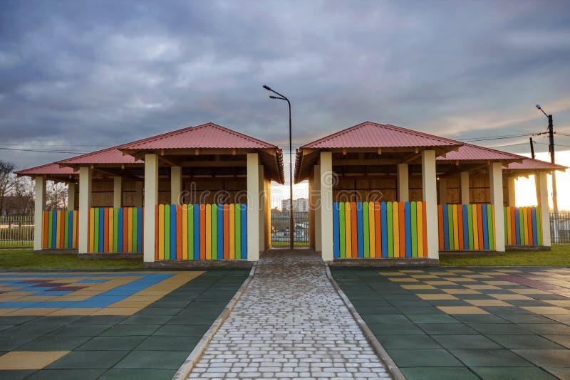 Campo de jogos do jardim de infância com a alcova nova brilhante com a baixa cerca colorido, jarda grande com o revestimento de b imagem de stock