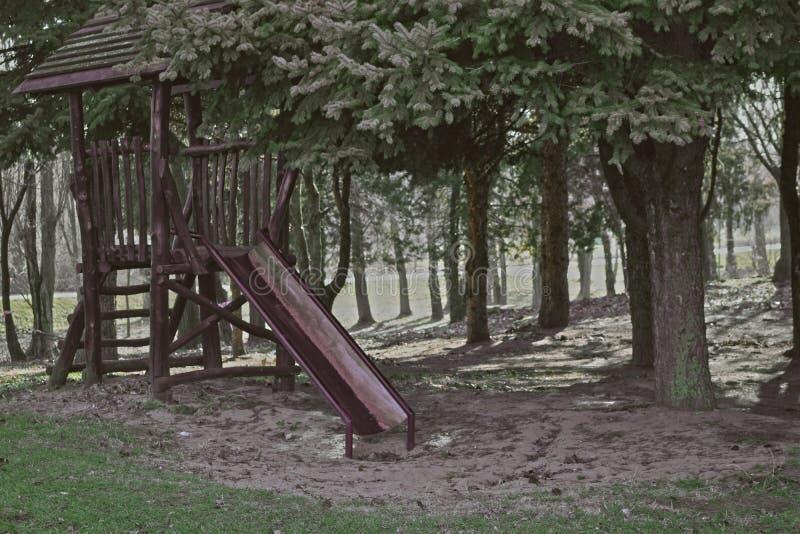Campo de jogos exterior da aventura para crianças Equipamento de madeira do campo de jogos com corrediças no tempo de mola imagem de stock royalty free